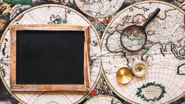 Magnifying glass and compass near empty blackboard Free Photo