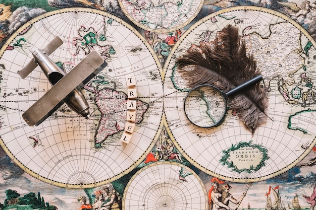 Magnifying glass and feathers near travel writing and plane Free Photo