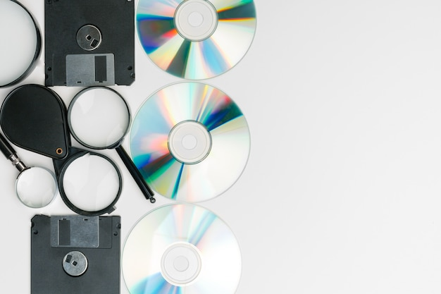Magnifying glass, floppy disk and cd Premium Photo