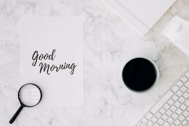 Magnifying glass on good morning paper with coffee cup; diary and keyboard on white marble desk Free Photo