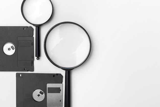 Magnifying glass inspecting on floppy disk concept Premium Photo