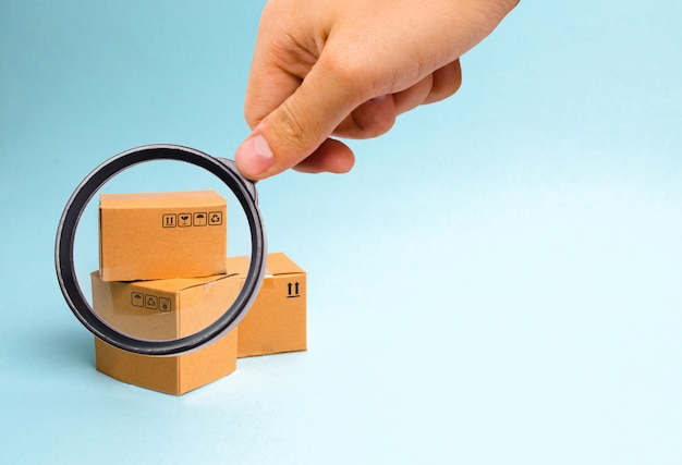 Magnifying glass is looking at the bunch of boxes on a blue background. Premium Photo