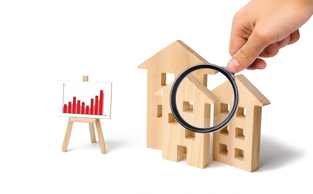 Magnifying glass is looking at the wooden houses Premium Photo
