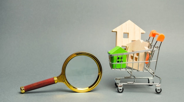 Magnifying glass and miniature wooden houses. Premium Photo