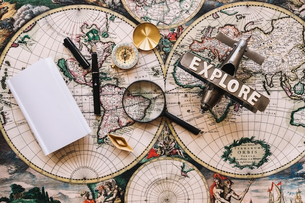 Magnifying glass near old compass and plane Free Photo