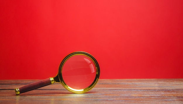 Magnifying glass on a red background. search and analysis, analytics and study. Premium Photo
