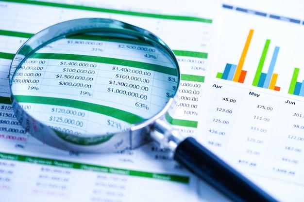 Magnifying glass on spreadsheet paper. Premium Photo