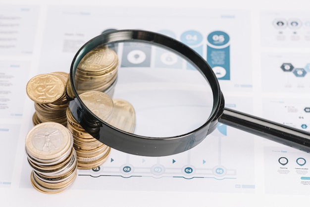 Magnifying glass over the stack of coins on infographic template Free Photo
