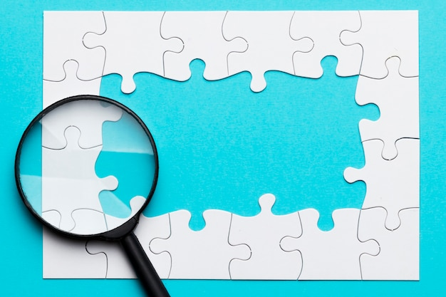 Magnifying glass over white jigsaw puzzle frame over blue surface Free Photo
