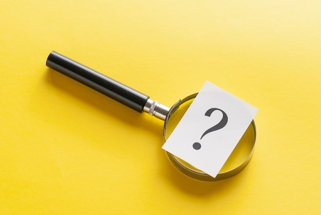 Magnifying glass with question mark on yellow Premium Photo