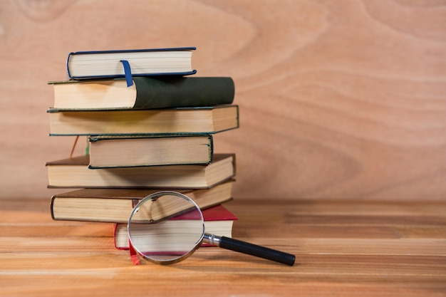 Magnifying glass with stack of books on a table Free Photo