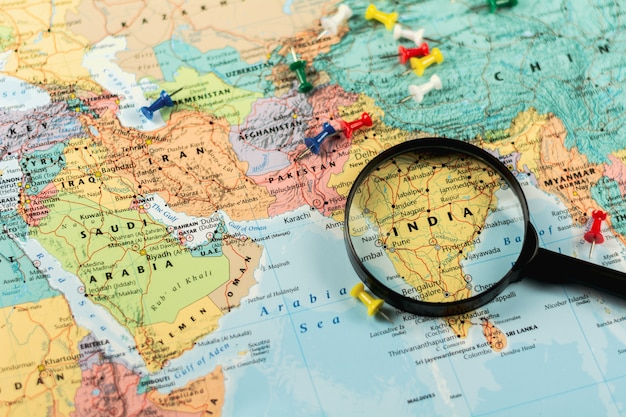 Magnifying glass on the world map selective focus at india. - economic and business concept. Premium Photo