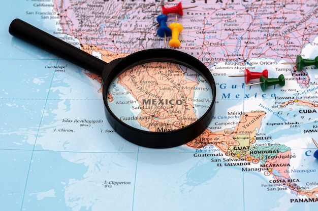 Magnifying glass on the world map selective focus at mexico map. - economic and business concept. Premium Photo