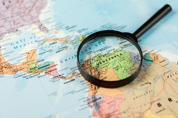 Magnifying glass on the world map selective focus at venezuela. - economic crisis concept. Premium Photo