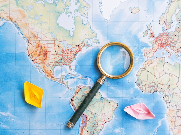 Magnifying glass on world map Free Photo