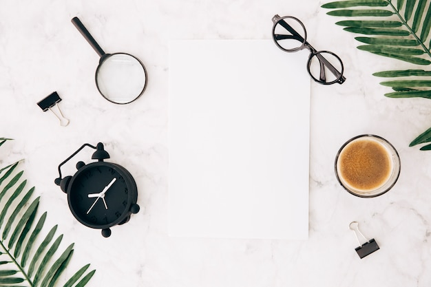 Magnifying glasses; alarm clock; eyeglasses; coffee; bulldog clip and leaves with blank white paper on marble textured backdrop Free Photo