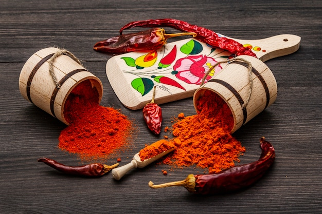 Magyar red sweet and hot paprika powder. traditional pattern on a cutting board, different varieties of dry pepper. black wooden Premium Photo