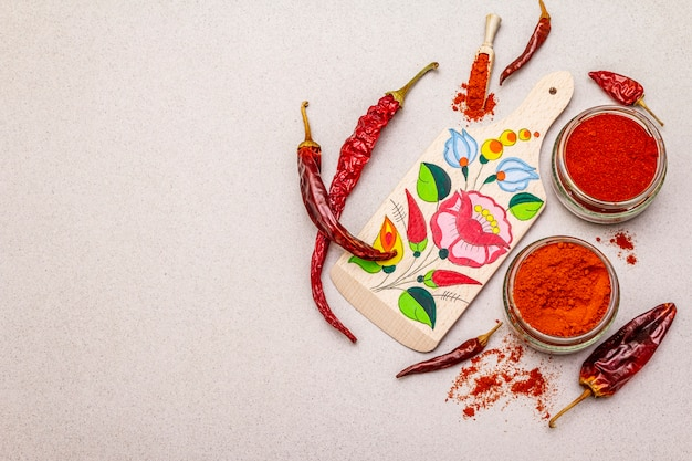 Magyar red sweet and hot paprika powder. traditional pattern on a cutting board, different varieties of dry pepper. stone concrete Premium Photo