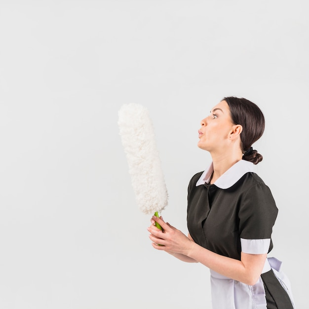 Maid blowing on duster Free Photo