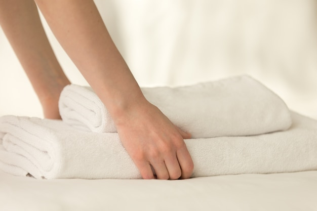 Maid placing stack of towels on the bed Free Photo