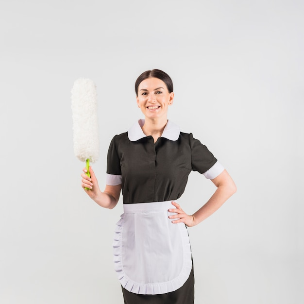 Maid with duster smiling Free Photo