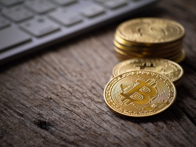 Make bitcoins golden color on the keyboard and the working table with close up view Premium Photo