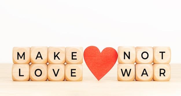 戦争ではなく恋を引用する。テーブルの上にテキストとハートの木製ブロック。 Premium写真
