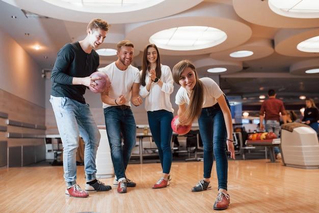 Fai un bel tiro. i giovani amici allegri si divertono al bowling durante i fine settimana Foto Gratuite