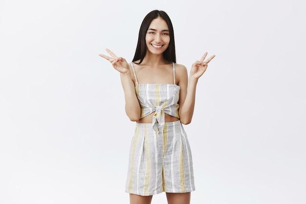 Fai la pace, non la guerra. ritratto di modello femminile asiatico alla moda attraente con capelli scuri lunghi in top e pantaloncini abbinati, mostrando segni di vittoria e sorridendo ampiamente, in posa per la foto del profilo Foto Gratuite