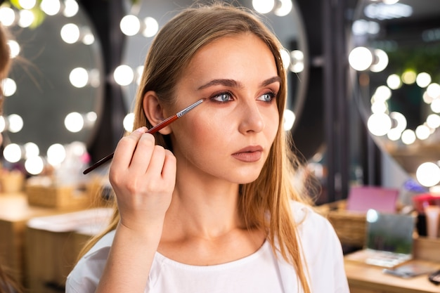 Make-up artist applying eyeshadow on face Free Photo