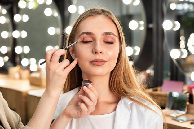 Make-up artist applying eyeshadow on woman Free Photo