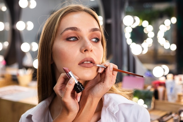 Make-up artist applying lipstick on smiling woman's lips with brush Free Photo