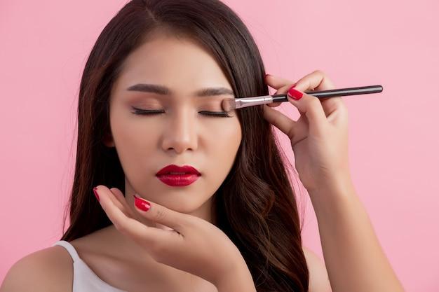 Make-up artist applying liquid eyeliner with brush Free Photo