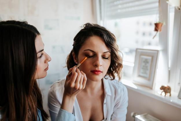 Make-up artist applying make-up on a beautiful girl. close-up. Premium Photo