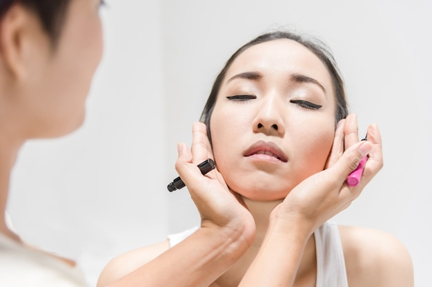 Make up artist applying make up to clean face a fashion model or bride Premium Photo
