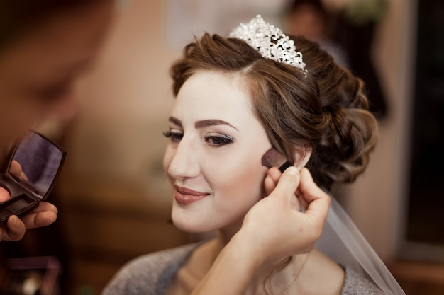 Make-up artist doing makeup to the bride on the wedding day. Premium Photo