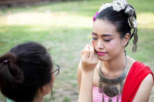 Make up artist making up eye liner to thai woman wearing thai traditional clothing Premium Photo