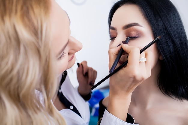 Make-up artist preparing beautiful bride for ceremony in a morning Premium Photo