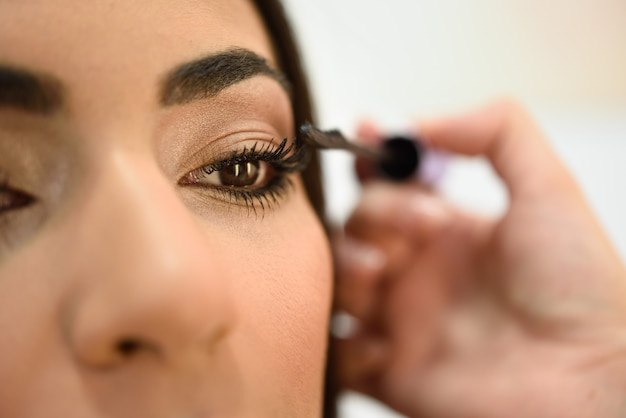 Make-up artist putting on the eyelashes of an african woman Premium Photo
