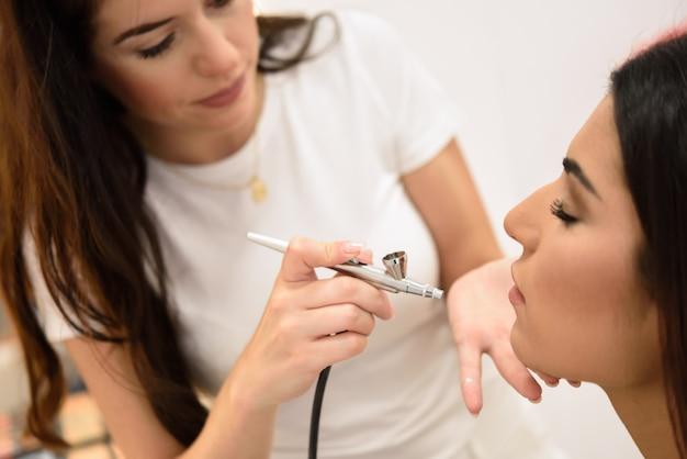 Make-up artist using aerograph making an airbrush make up Premium Photo