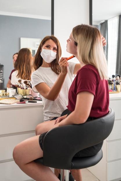 Make-up artist indossando mascherina medica da dietro il colpo Foto Gratuite