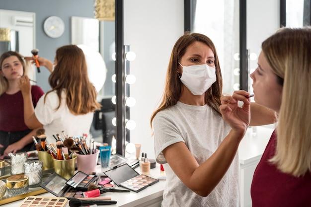 Make-up artist che indossa la maschera medica riflesso nello specchio Foto Gratuite
