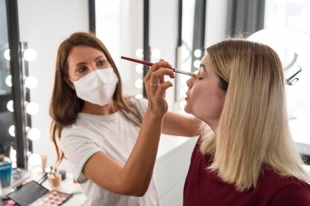 Make-up artist che indossa la maschera medica vista laterale Foto Gratuite