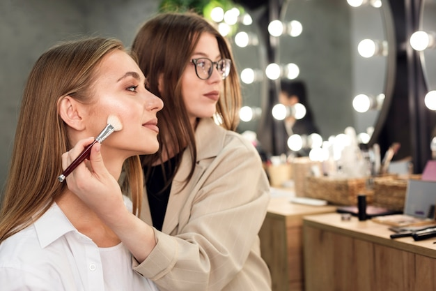 Make-up artist and woman looking at mirror applying contouring Free Photo