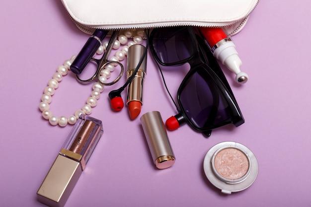紫色の背景に分離された化粧品でバッグを作る Premium写真