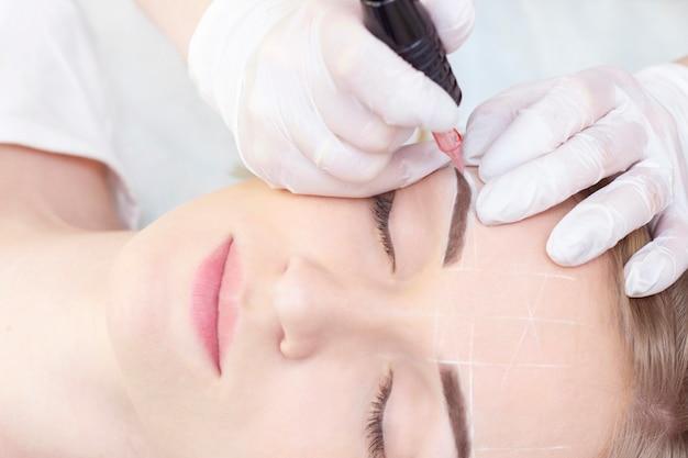 Составить. косметолог руки делают татуаж бровей на лице женщины. перманентный макияж бровей в салоне красоты. макрофотография специалист делает брови татуировки для женщин. косметология лечение. Premium Фотографии