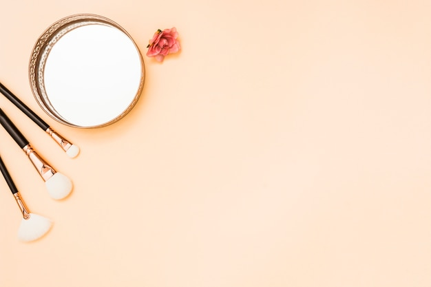 Make-up brushes; circular mirror and rose on beige backdrop Free Photo