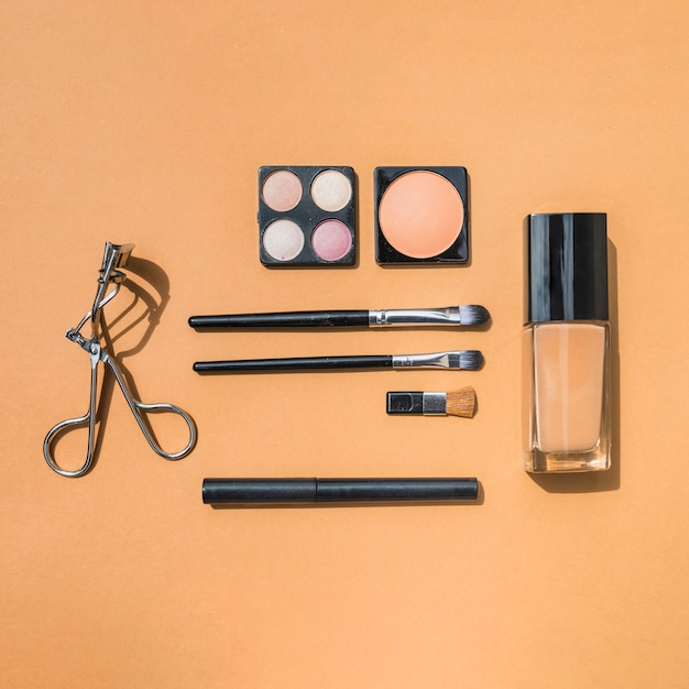 Make up and cosmetic beauty products on ochre backdrop Free Photo