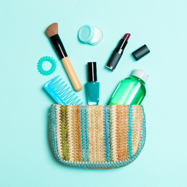 Make up products spilling out of cosmetics bag on blue pastel background with empty space Premium Photo