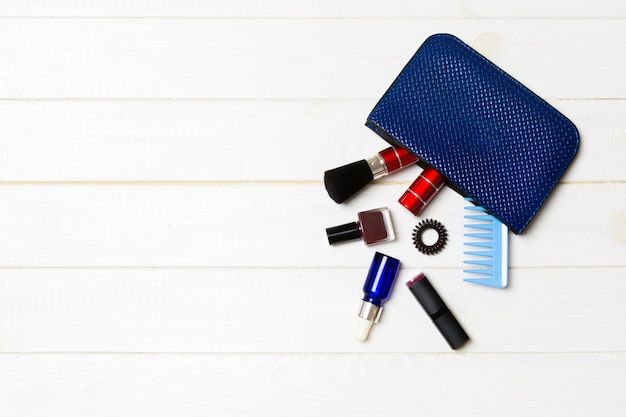 Make up products spilling out of cosmetics bag on white wooden Premium Photo